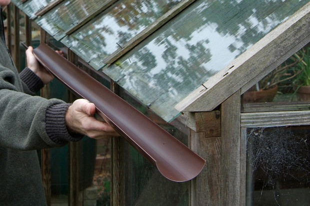 checking-the-length-of-a-piece-of-guttering-against-the-side-of-the-greenhouse-2