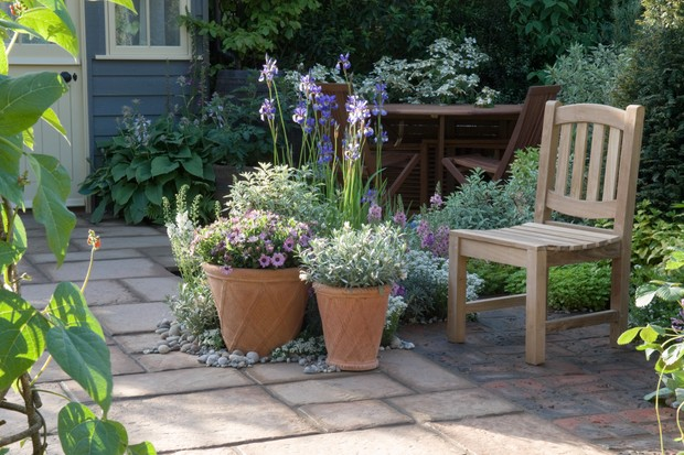 Planted terracotta pots and garden furniture arranged on a well-swept patio