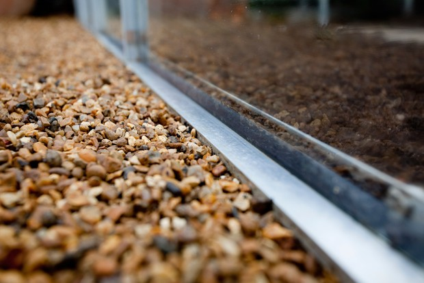 Gravel path next to a greenhouse
