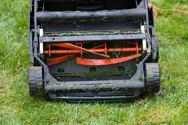 A front view of a cylinder mower, with the spindle of curved red blades clearly visible