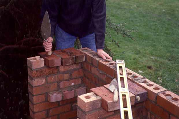 putting-bricks-side-on-to-create-a-barbecue-shelf-support-2