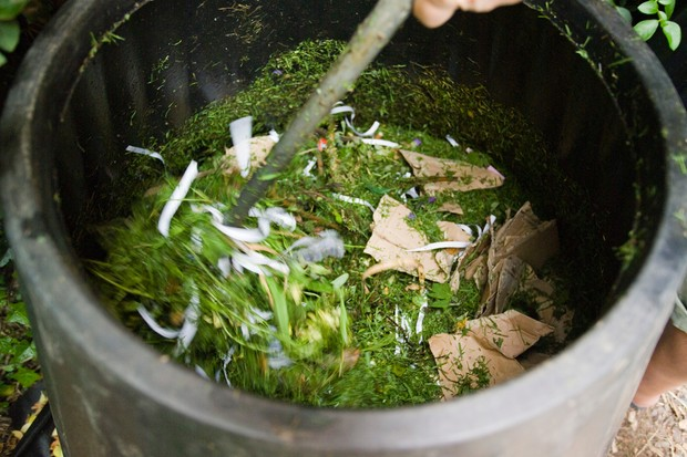 Stirring to mix together grass clippings and paper and card shreddings