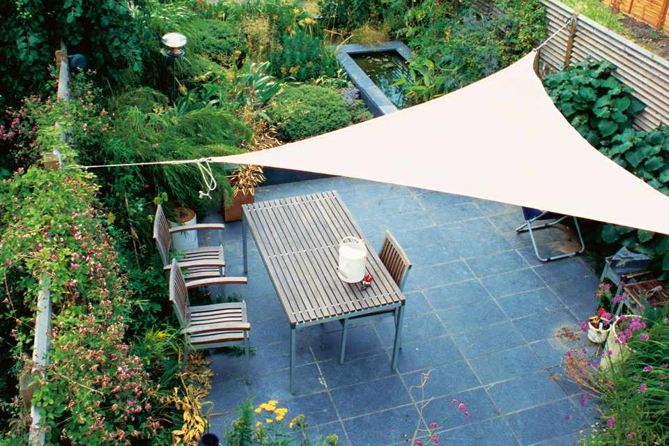 A shade sail over a patio seating area