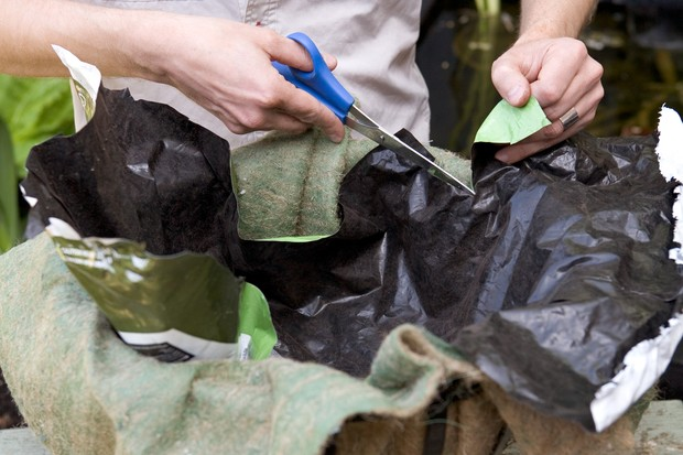 Adding an old plastic bag to the hanging basket liner to aid moisture retention