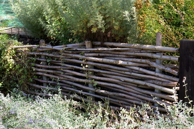 A fence made of branches woven between sturdy posts