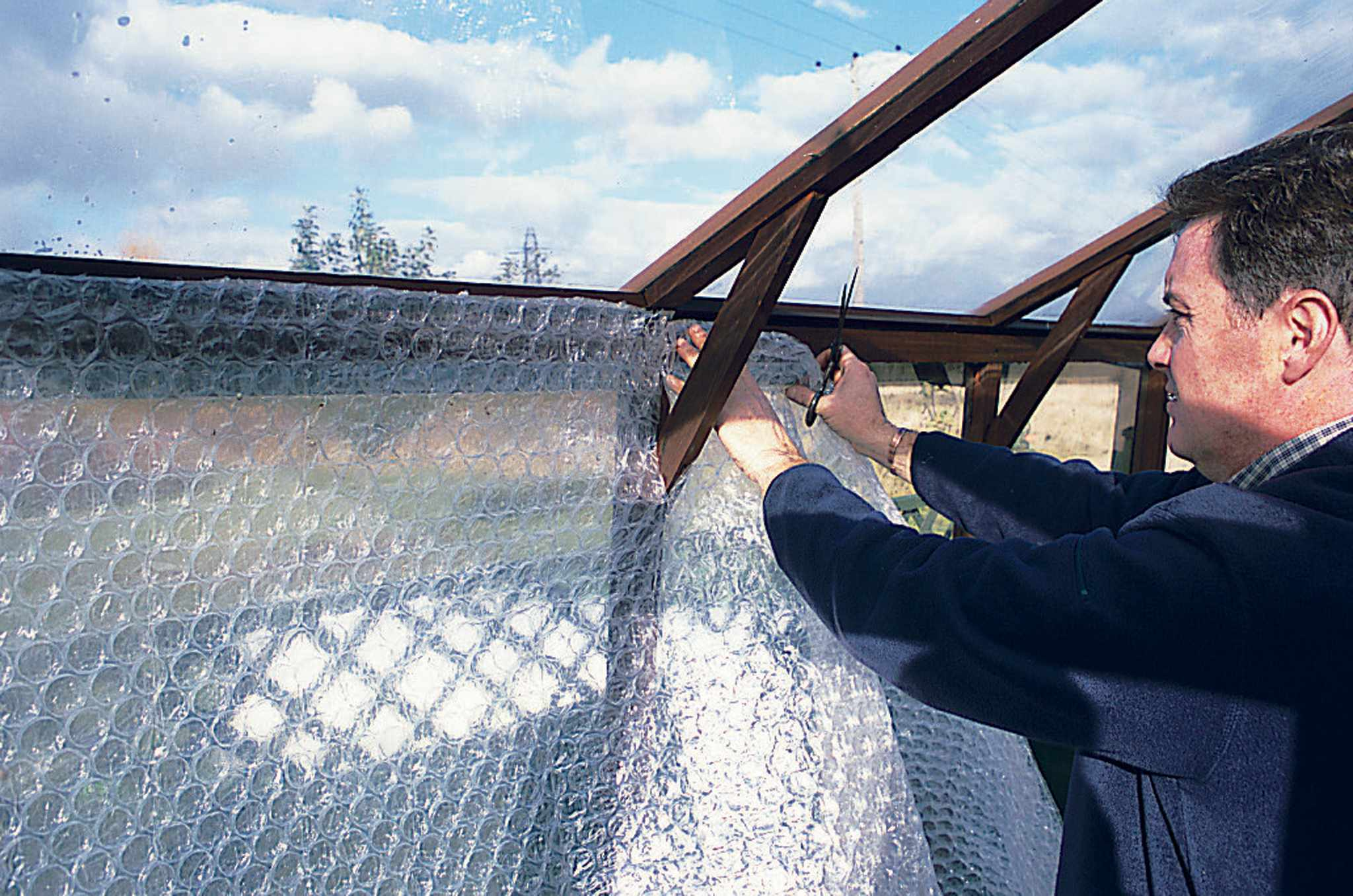 Fixing bubble wrap to the greenhouse frame