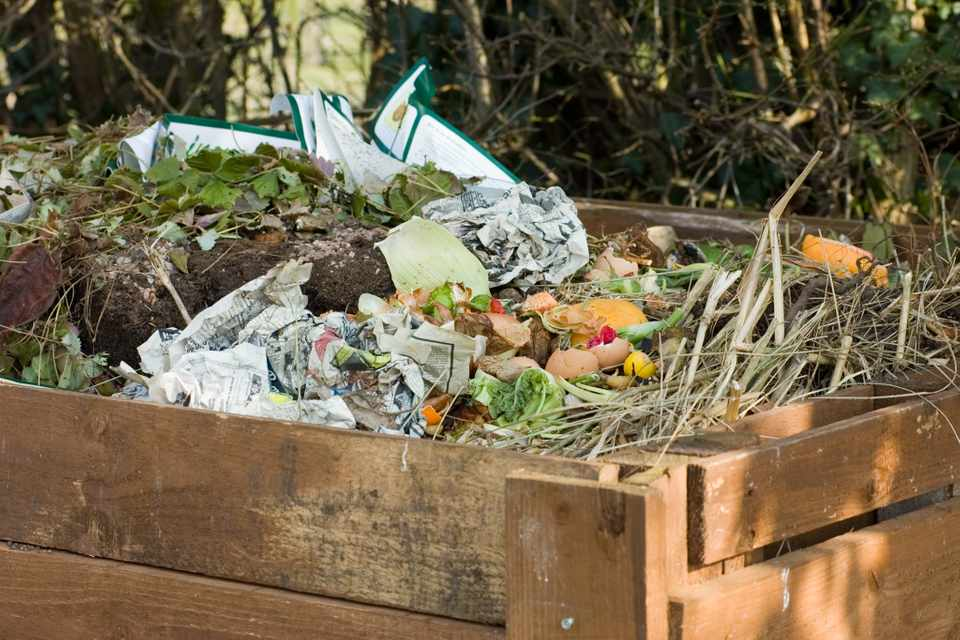 An open-topped compost heap with sides made of wooden slats