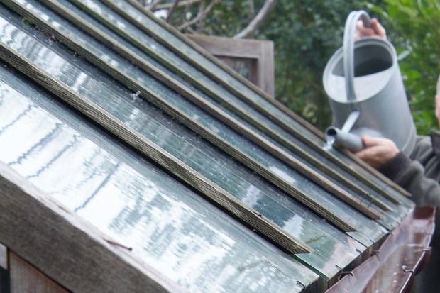 pouring-water-into-the-guttering-from-a-watering-can-to-test-that-the-water-flows-smoothly-2