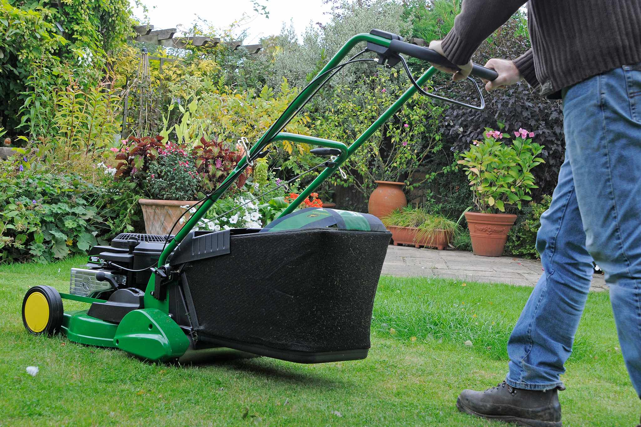 Mowing a lawn with a petrol mower