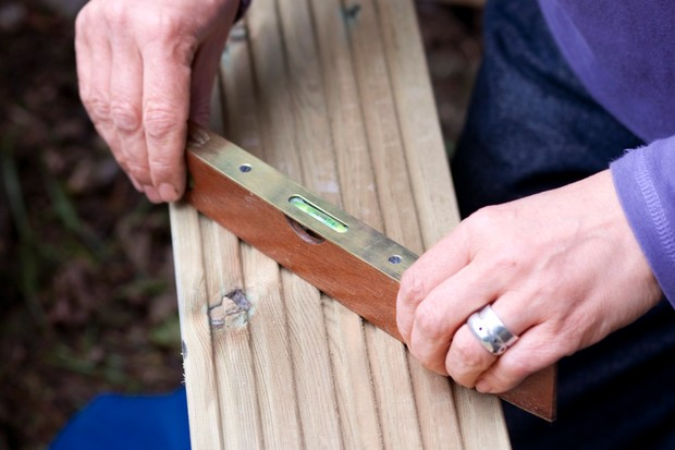 Using a spirit level to check the sides are level