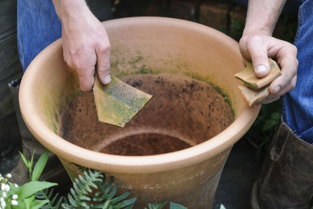 Hosta and fern pot display - adding crocks