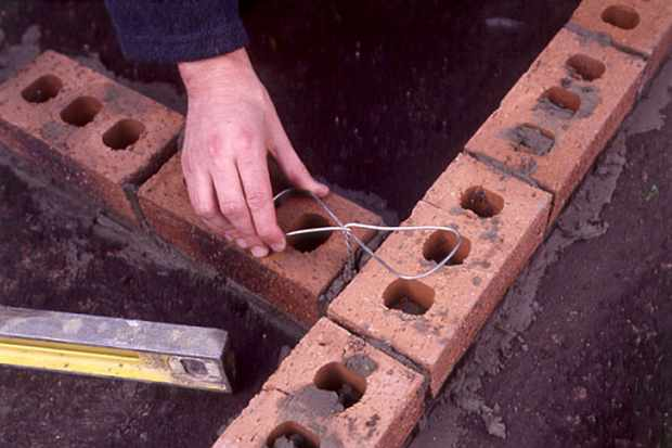 inserting-metal-tie-into-mortar-of-barbecue-2