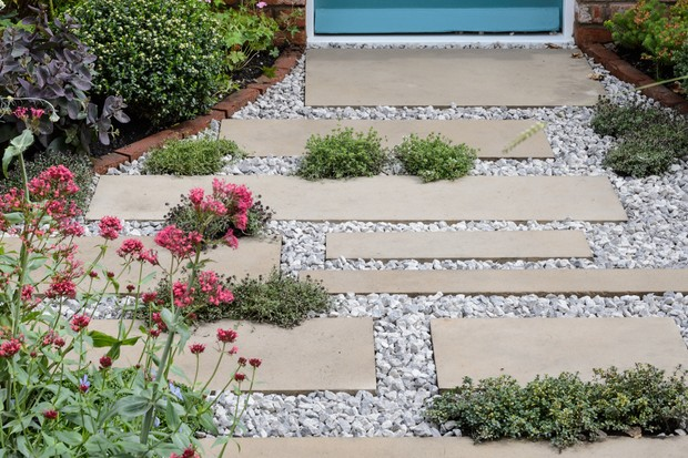 Garden path with plants growing between the slabs
