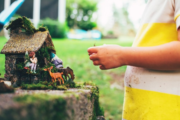 Child playing with fairy garden, Getty