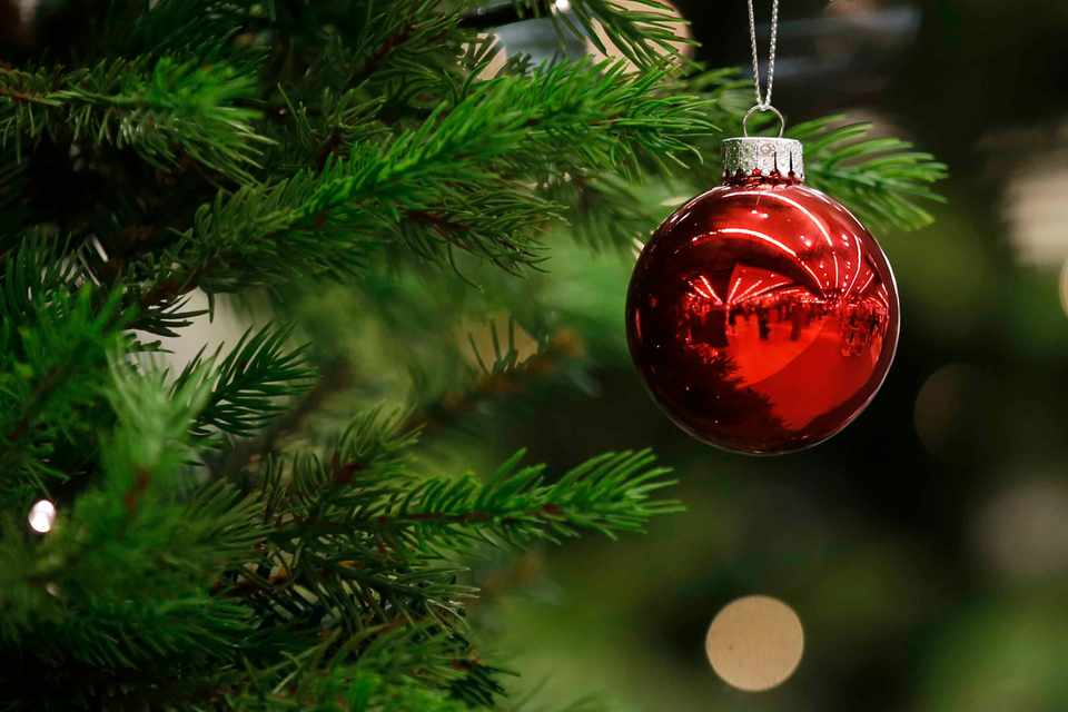 A Christmas bauble hangs from a tree inside a store in the U.K. Photographer: Luke MacGregor/Bloomberg