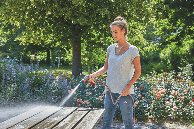 A lady washing down a bench with a hose