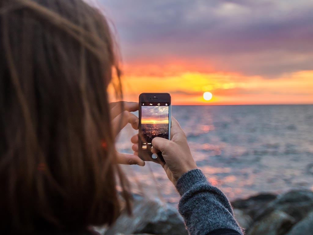 Woman taking a photo of a sunset