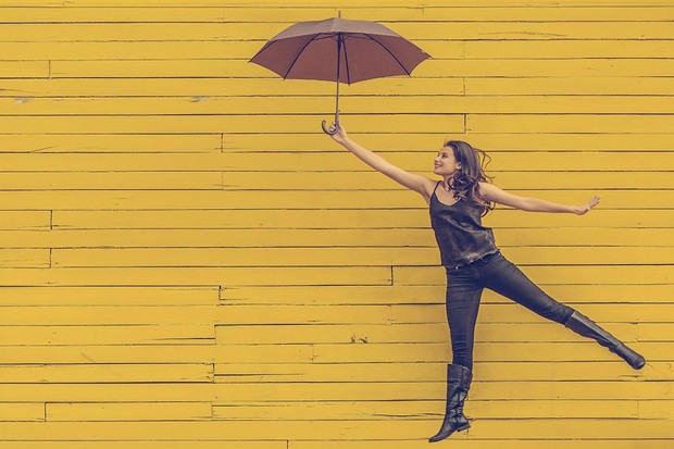 Woman jumping with umbrella
