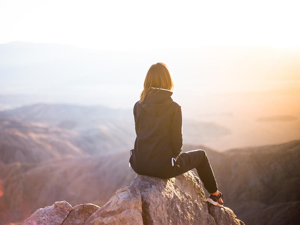 Woman sitting on top of a mountain