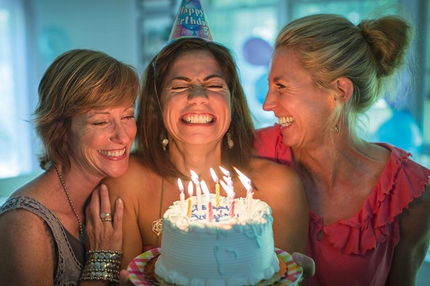 Mature woman holding birthday cake, making wish while two friends look on