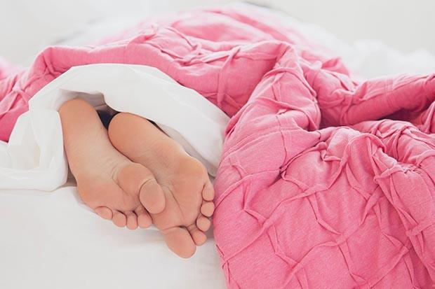Woman's feet under a duvet