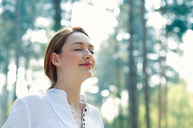 Woman with eyes closed in woodland.
