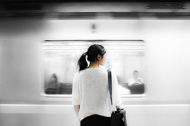 Dark-haired woman waiting on a train station platform