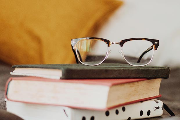 A pair of glasses on a stack of books