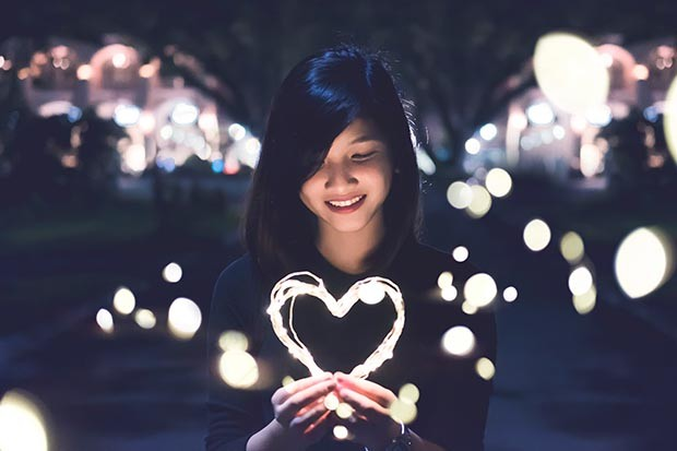 Smiling woman holding a heart made of fairy lights