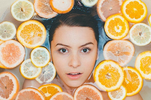 Woman lying in a bath with sliced citrus fruits