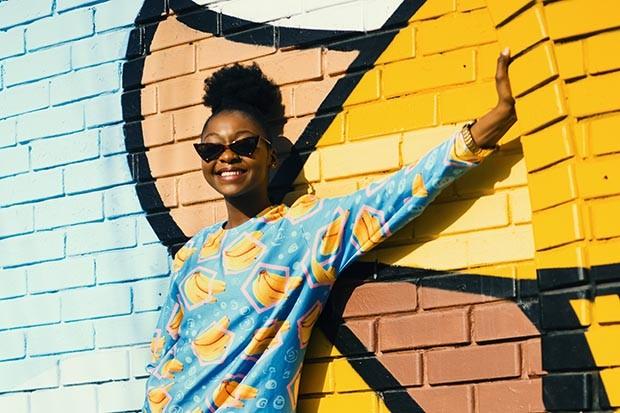 Cheerful woman leaning against a graffiti wall