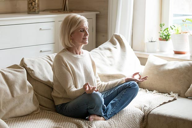 Older woman meditating at home