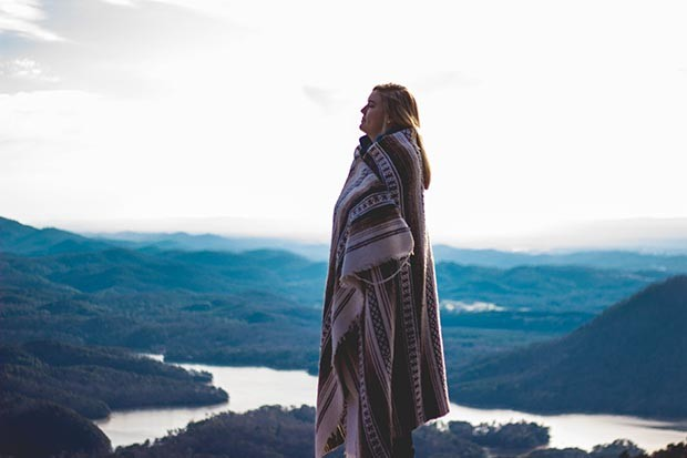 Woman wrapped in a blanket standing on a mountain