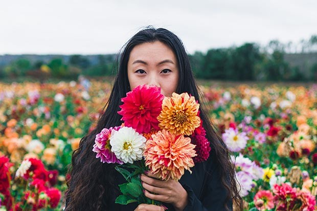 Woman in a field surrounded by flowers
