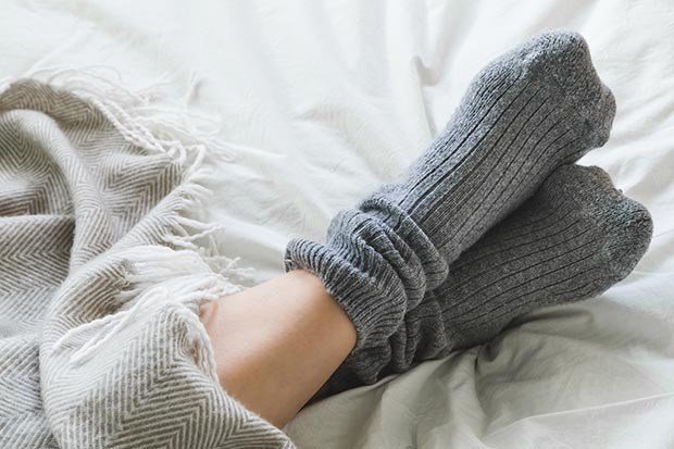 Feet crossed with gray socks on bed under blanket
