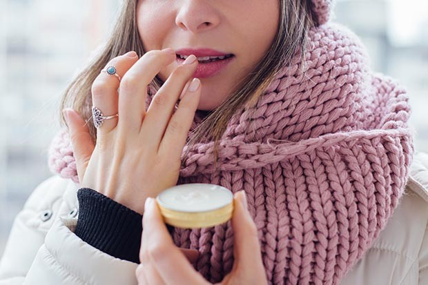 Woman applying lip balm in cold weather