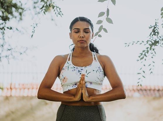 Dark-haired woman practising yoga outside