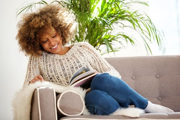 African American woman reading a book on a sofa