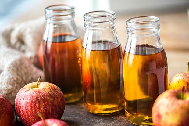 Apple cider vinegar in jars surrounded by apples