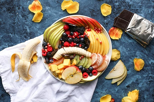 Bowl of fruit surrounded by petals