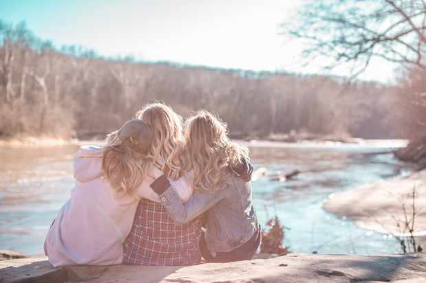 Three women hugging each other beside a river