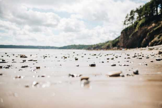 Stones and sand on a clear beach, by Rachael Smith / Our Beautiful Adventure