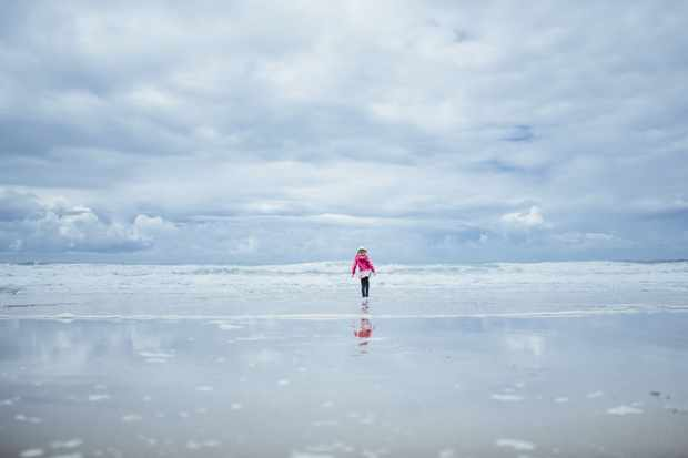 Standing alone on the beach with blue sky, by Rachael Smith / Our Beautiful Adventure