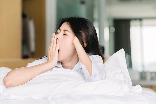 Asian woman yawning after waking up