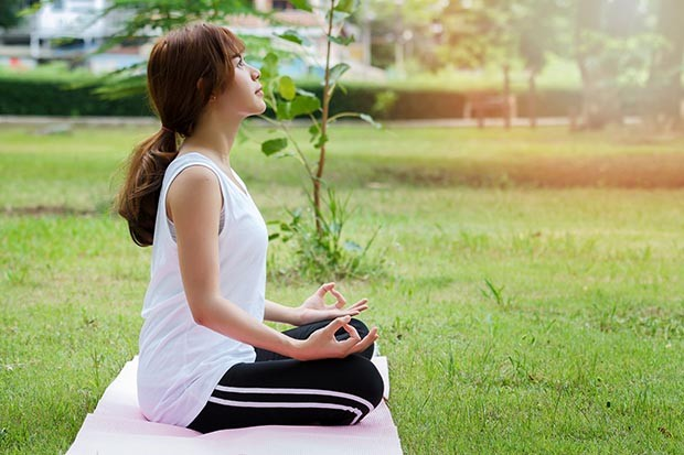 Young asian woman in sportswear meditating while sitting in lotus pose on yoga mat