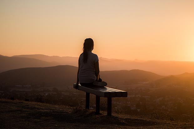 Woman sitting on a bench meditating