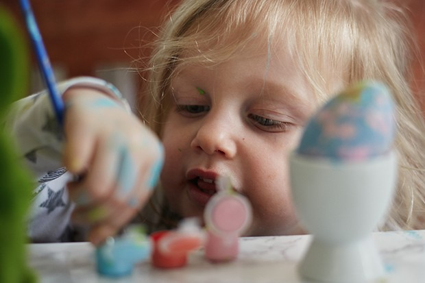 Child painting easter eggs