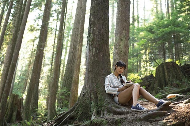 Woman writing in journal against tree in woods