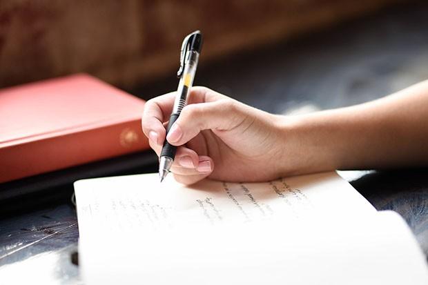 womans-hand-holding-pen-hannah-olinger-8eSrC43qdro-unsplash