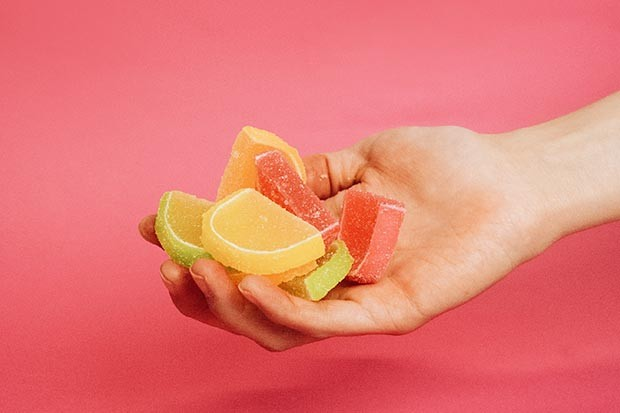 Hand holding jelly citrus slices